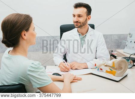 Young Mixed Race Audiologist Consults A Woman Patient In His Office. Treatment Of Hearing Loss In Ad