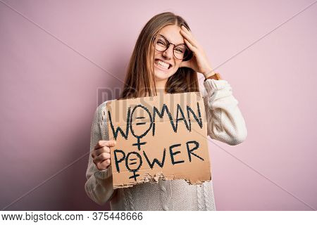 Young beautiful redhead woman asking for women rights holding banner over pink background stressed with hand on head, shocked with shame and surprise face, angry and frustrated. Fear and upset
