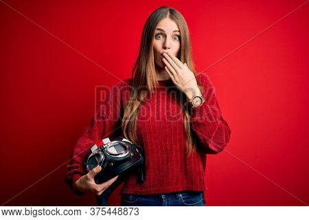 Young beautiful redhead motocyclist woman holding moto helmet over red background cover mouth with hand shocked with shame for mistake, expression of fear, scared in silence, secret concept