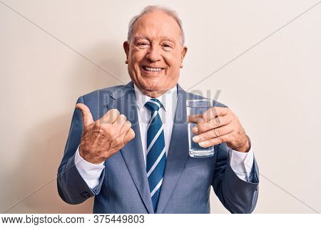 Senior handsome grey-haired businessman wearing suit drinking glass of water to refreshment pointing thumb up to the side smiling happy with open mouth