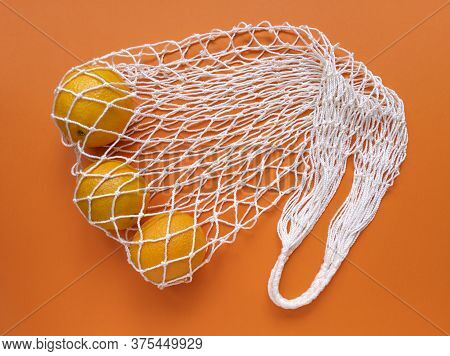White String Cotton Eco Bag With Oranges On Orange Background. Monochrome Simple Flat Lay. Ecology Z
