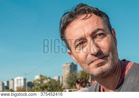 Outdoor Portrait Of An Handsome Brunet Man At The Park With Blue Sky And Urban Background. Spending