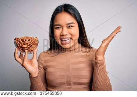 Young asian girl holding bowl with baked german pretzels over isolated white background very happy and excited, winner expression celebrating victory screaming with big smile and raised hands