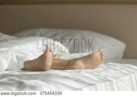 The Legs Protruding From The Blanket. The Tip Of The Foot Extends From The Blanket.