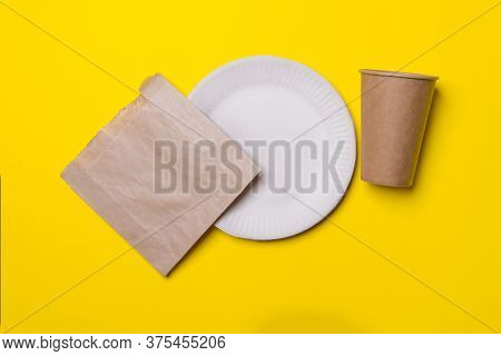 Eco Friendly Kitchen Ware, Plate, Cup, Bag, In Yellow Colored Paper Background. Top View. Close-up.