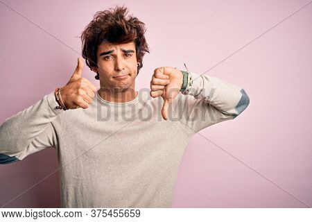 Young handsome man wearing casual t-shirt standing over isolated pink background Doing thumbs up and down, disagreement and agreement expression. Crazy conflict