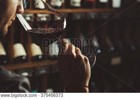 Close-up Shot Of Young Sommelier Smell Red Wine On Wine Cellar Background.