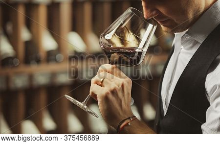 Male Sommelier Tasting Red Wine At Cellar.
