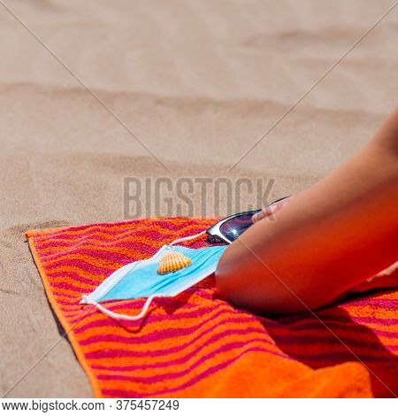 closeup of a caucasian man, lying face down on a colorful orange towel on the beach, next to his sunglasses, a seashell and a blue surgical mask