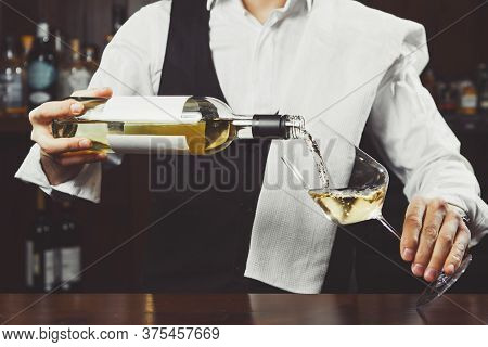 Sommelier Pours White Wine To Wineglass On Bar Counter Background, Close-up View.