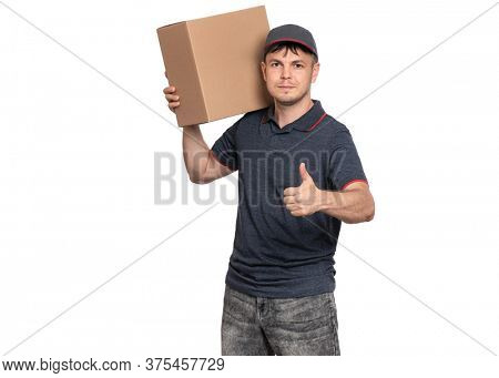 Portrait of Delivery man in cap holding big cardboard box. Handsome man making Thumb up gesture and looking on camera. Courier isolated on white background.