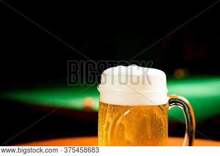 Mug With Draft Beer On A Table With Pool Table Behind