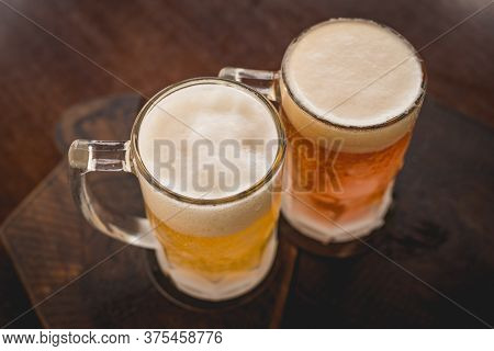 Two Mugs Of Chopp On The Table