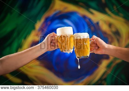 Two People Toasting With Mugs Full Of Draft Beer With Stylized Brazilian Flag Background