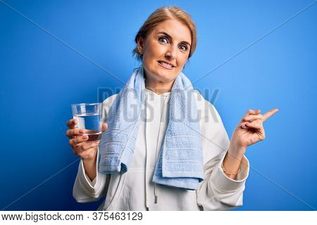 Middle age beautiful blonde sportswoman wearing towel drinking glass of water to refreshment very happy pointing with hand and finger to the side
