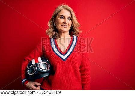 Middle age beautiful blonde motorcyclist woman holding moto helmet over red background with a happy face standing and smiling with a confident smile showing teeth