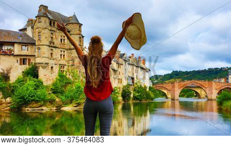 woman happy traveling in France-Aveyron, Estaing