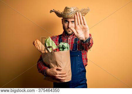 Young rural farmer man holding fresh groceries from marketplace over yellow background with open hand doing stop sign with serious and confident expression, defense gesture