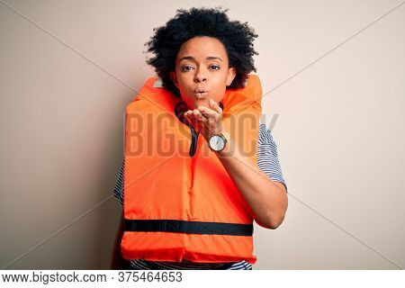 Young African American afro woman with curly hair wearing orange protection lifejacket looking at the camera blowing a kiss with hand on air being lovely and sexy. Love expression.