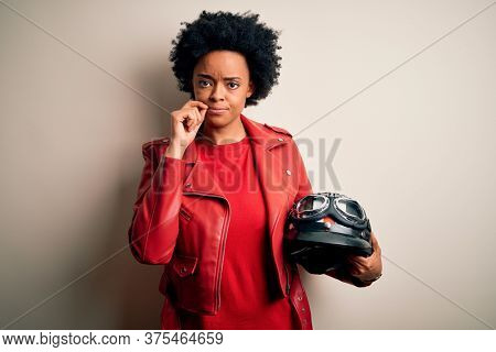 Young African American afro motorcyclist woman with curly hair holding motorcycle helmet mouth and lips shut as zip with fingers. Secret and silent, taboo talking