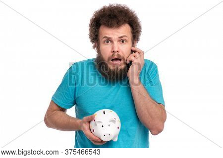 Crazy bearded Man with funny Curly Hair holding Piggy Bank, isolated on white background. Saving Money concept. Scared or Shocked Male with piggybank.