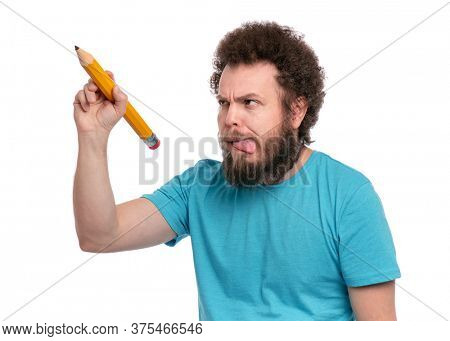 Crazy bearded Man with funny Curly Hair holding Big Pencil, isolated on white background. Happy Guy writing something and looking away.