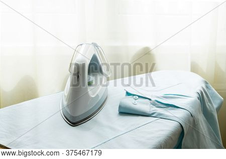 The Electric Iron Horizontally Worth It On The Ironing Board On The Men's Shirt Prepared For Ironing