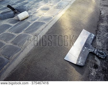 A Large Metal Facade Spatula Lies On The Surface Of The Concrete Screed, And A White Rubber Mallet L