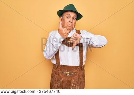 Senior grey-haired man wearing german traditional octoberfest suit over yellow background Doing thumbs up and down, disagreement and agreement expression. Crazy conflict
