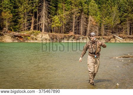 Kitimat,  British Columbia, Canada - July 27th, 2015: A Sport Fly Fisherman Hooked Into A Salmon On
