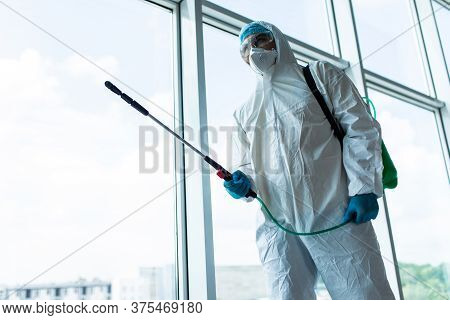 Coronavirus Pandemic. A Disinfector In A Protective Suit And Mask Sprays Disinfectants Inoffice. Pro