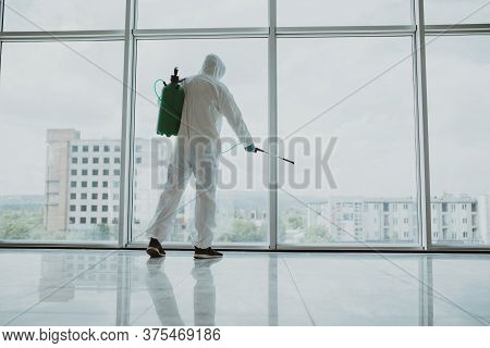 Man Disinfector Worker Cleaning Office Space And Window Before Work On Corona Virus Pandamia.