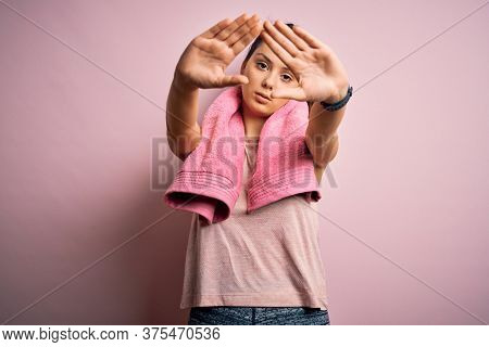 Young beautiful brunette sportswoman wearing sportswear and towel over pink background doing frame using hands palms and fingers, camera perspective