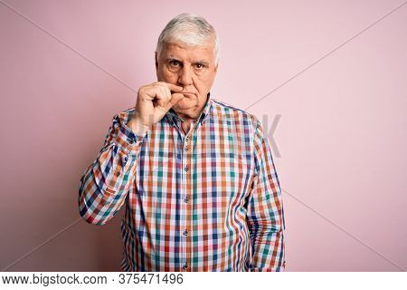 Senior handsome hoary man wearing casual colorful shirt over isolated pink background mouth and lips shut as zip with fingers. Secret and silent, taboo talking