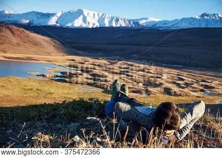 Hikers Lie Down Taking Resting After Long Walk At Top Of Mountain. Altai