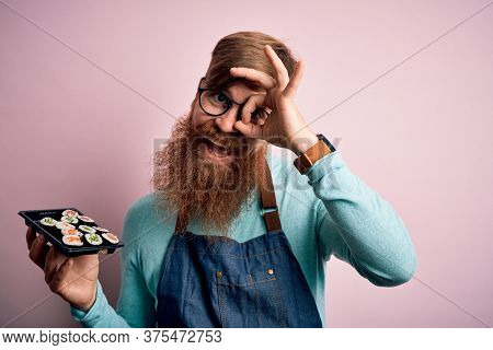 Redhead Irish cook man with beard holding maki sushi tray over isolated background with happy face smiling doing ok sign with hand on eye looking through fingers