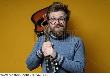 Funny Hipster In An Old Sweater Holds An Acoustic Guitar On Shoulder And Looks At The Camera With A
