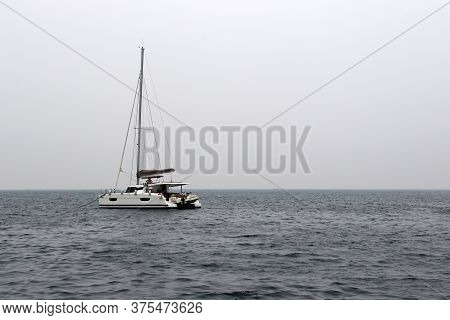 White Single-masted Yacht With A Deflated Sails In The Open Sea. Seascape In Storm Weather, Travel A