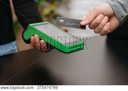 Closeup Of Male Right Hand Holding Bank Credit Card On A Nfc Payment Terminal Held By A Woman\'s Han
