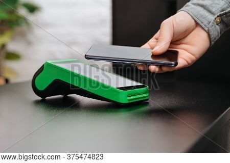 Man Paying Bill Through Smartphone Using Nfc Technology In A Shop. Male Customer Paying Through Mobi