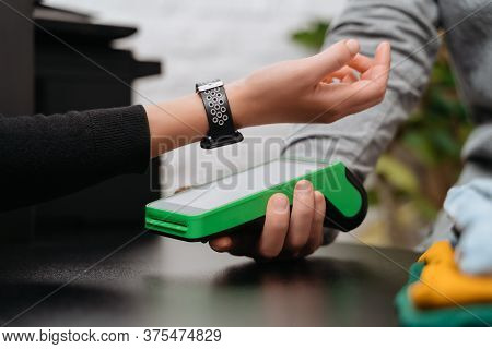Closeup Of Woman Paying For Purchase Through Smartwatch Using Nfc Technology In A Clothing Store. Cl