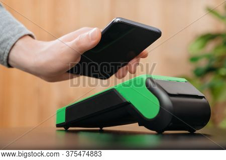 Closeup Of Man's Hand Holding Smartphone Near Nfc Payment Terminal. Customer Using Phone For Contact
