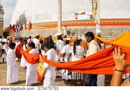 Anuradhapura, Sri Lanka - 21 Feb 2016: A Procession Of People Dressed In White Wraps A 366 Meter-lon