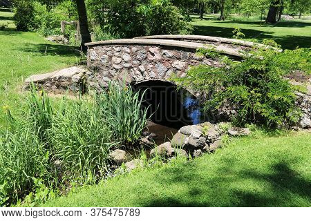 A Country Stream Flowing Through A Rock Wall Bridge With Lush Foliage And Shadows