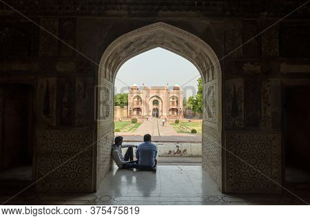 Agra, India - 4 May 2015: Two Men Sit In The Shade Of Itimad Ud Daulah Tumb Mausoleum In Agra, India