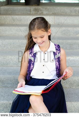 Back To School. Education Concept. Cute Smiling Schoolgirl Sitting On A Steps Outdoor. Happy Little