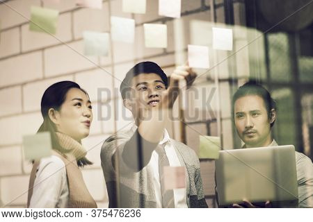 Three Asian Small Company Businesspeople Young Entrepreneurs Meeing Discussing In Office Using Stick