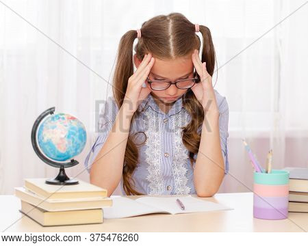 Education Concept. Little Cute Girl Child In Glasses Is Bored And Tired To Study And Doing Her Homew