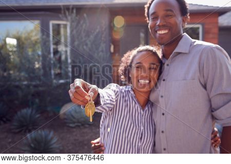 Portrait Of Couple Standing Outdoors In Front Of House With For Sale Sign In Garden Holding Keys