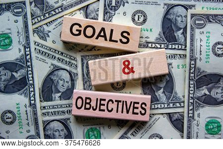 Concept Text 'goals And Objectives' On Wooden Blocks On A Beautiful Background From Dollar Bills.